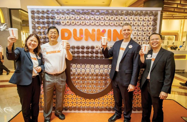 4 Dunkin' staff members holding up a Dunkin' coffee cups while standing in front of a wall lined up with Dunkin' Donuts