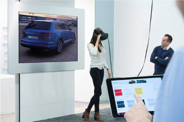 A woman is wearing a VR headset and a screen behind her is showing her seeing a blue SUV. A man is looking at her with his arms crossed. Another person is seen operating an Ipad at the corner of the room.
